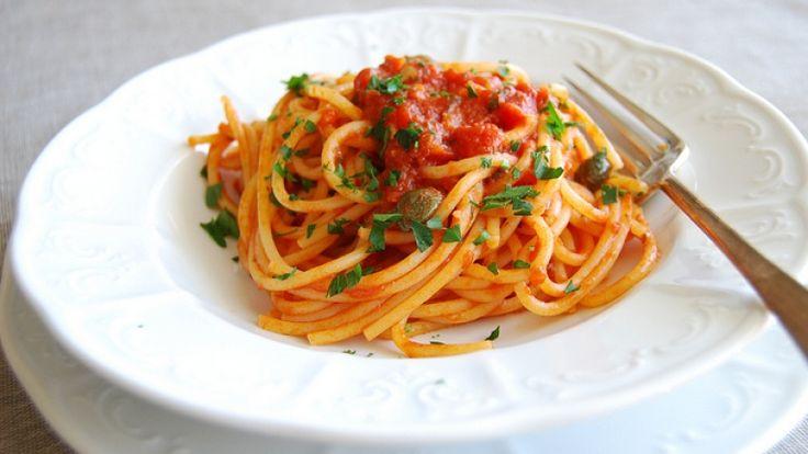 Spaghetti alla puttanesca ricetta e foto. Piatto di spaghetti con sugo, pomodoro