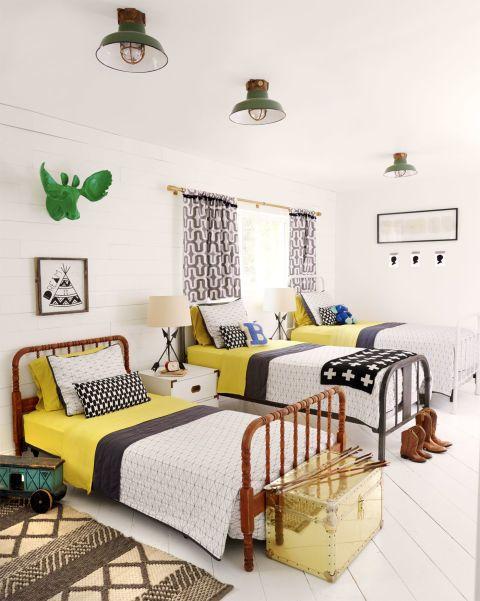 Tres marcos de la cama de la vendimia hacen dormitorio de estos niños en este rancho de Arizona mirada madura.  Ropa de cama a juego y un conjunto de viejas lámparas náuticas dan a la habitación un aspecto coherente.