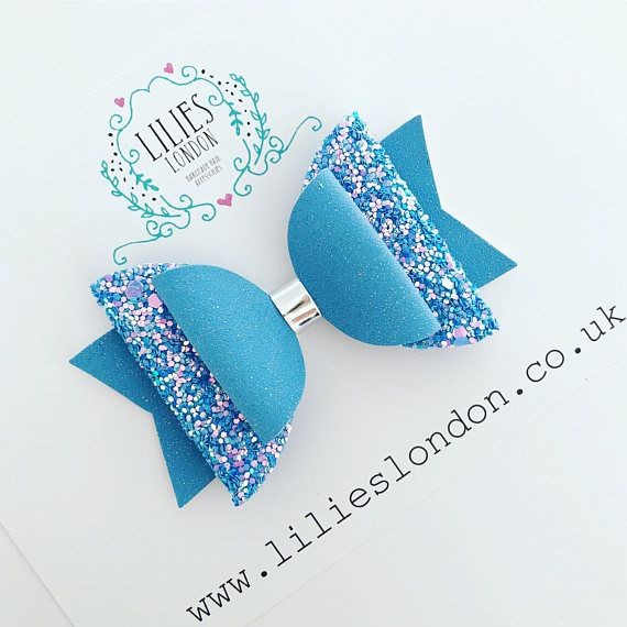 ABOUT ............ A super sparkly, bright blue, hair bow. This beautiful, glitter hair bow is perfect for children and adults alike. It would also add a little sparkle to a party outfit. The hair bow is made using high quality, non shedding, glitter fabric and a vegan suede fabric.