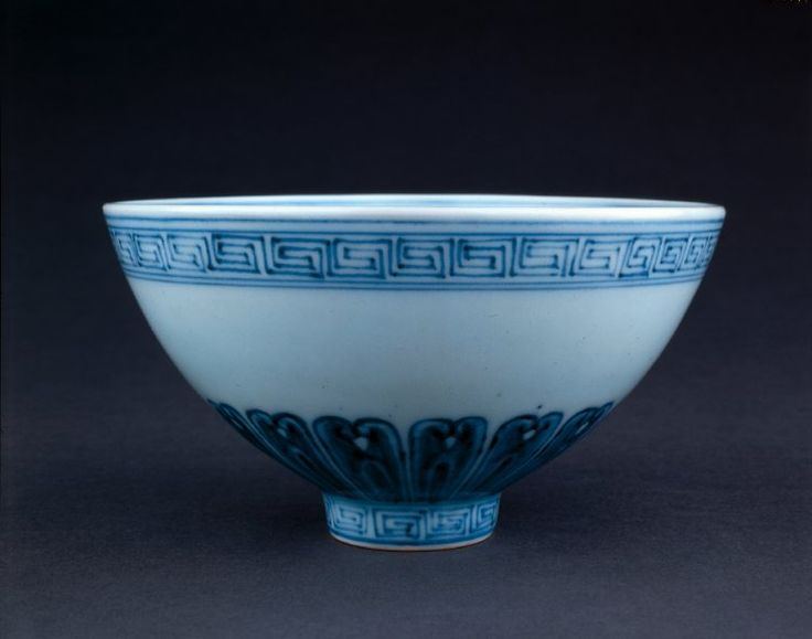 Porcelain bowl with flaring sides and deep foot, decorated in underglaze cobalt blue. Squared spirals at foot and rim, with separated lotus petals on the lower part of the body. Medallion on inside centre surrounded by flower heads and an arabesque band.
