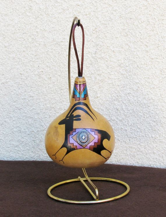 Hand-painted large gourd ornament with an antelope motif. Approx. Measurement: 5 H x 3.5 W Painted in rich earth tone colors, embellished with a concho button and featuring different front and back designs (as seen in the photos), this large gourd makes quite a statement. I painted the Southwest petroglyph-inspired antelope and the geometric design using matte and metallic colored acrylic paints. A satin cord is attached to the top for hanging on a tree branch or a display stand…