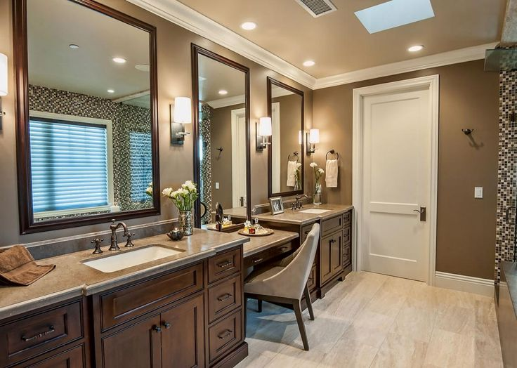 A trio of framed mirrors enhances the space in this long bathroom. With a double sink vanity and seating area, this bathroom provides generous storage and ample space to get ready for the day.
