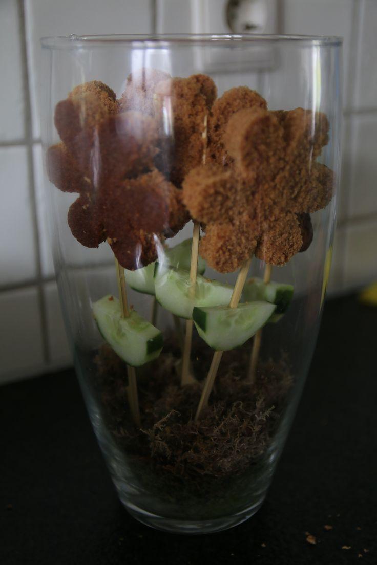 Een bloem gemaakt van ontbijtkoek, de blaadjes van komkommer.