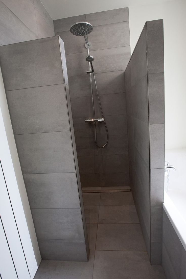 Walk in shower with large floor tiles and long grate