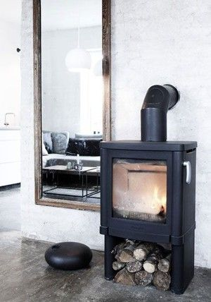 A wood stove is a cabin #essential Love the black metal against a white wall #thecabinologist