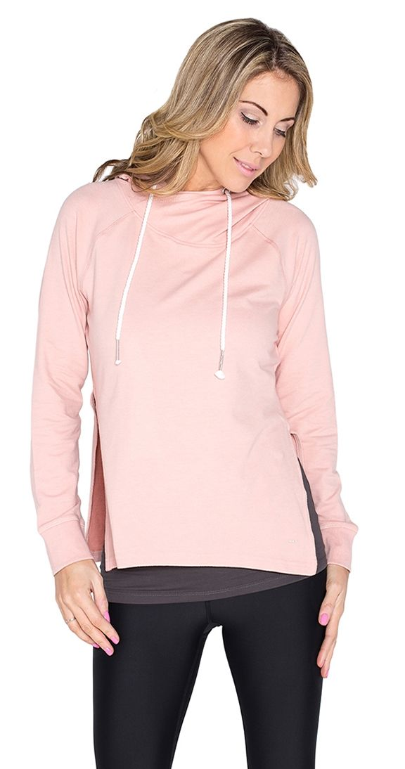 """Lotus Hoodie - blush. Be as one with your look and go to the studio in style. The Lotus Hoodie is in a higher fashion realm with the addition of cool side slits...hoodie on the top, inspired at the bottom. Wear it layered with a longer tank and your Cream of the Crop leggings (or denim for a different look). Peace out!  Model is wearing a M Twist drawstring on hood Long Sleeve Approx 27"""" length fr shoulder to hem Details 37% Cotton 34% Modal 24% Poly 5% Elastane"""