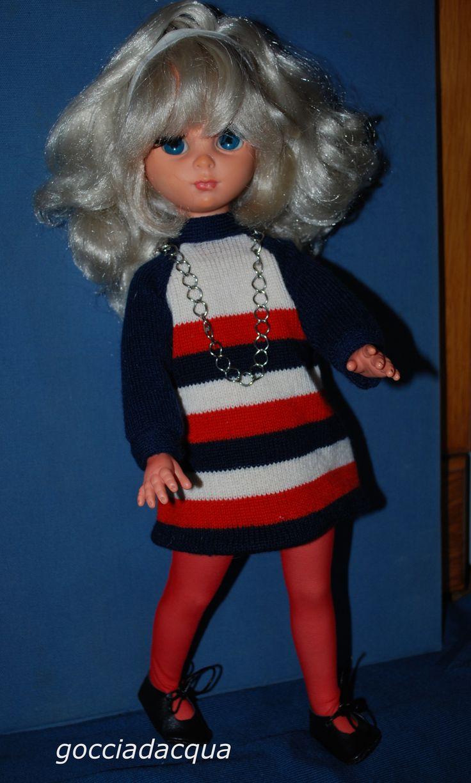 Susanna OOAK con capelli platino e pettinatura anni '60 con ampia frangia morbida trattenuta dalla fascia annodata; indossa miniabito mod in maglia di lana con collana a catena