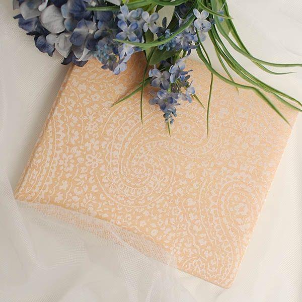 Perfekt für eine Hochzeit in zartem Apricot: Dieses hübsche Gästebuch ist mit feinen Stickereien im Paisley-Muster verziert. Echte Handarbeit!