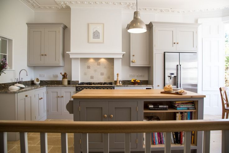A hand painted traditional Shaker kitchen with a blend of Oak and sandstone worktops and utilitarian centre island