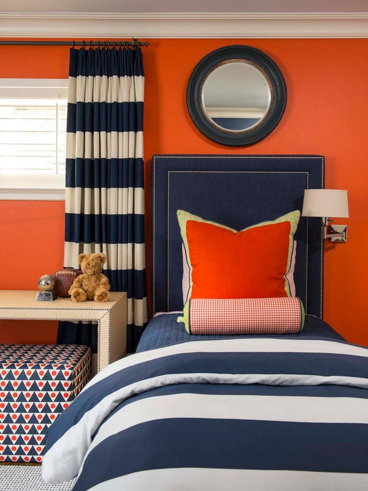 A bold orange accent wall creates a bright backdrop for the navy details in this boy's bedroom design. Thick navy and white stripes on the comforter match the striped curtains and upholstered navy headboard with small nailhead trim. Orange pillows and upholstered cube stools tie the accent wall into the design.