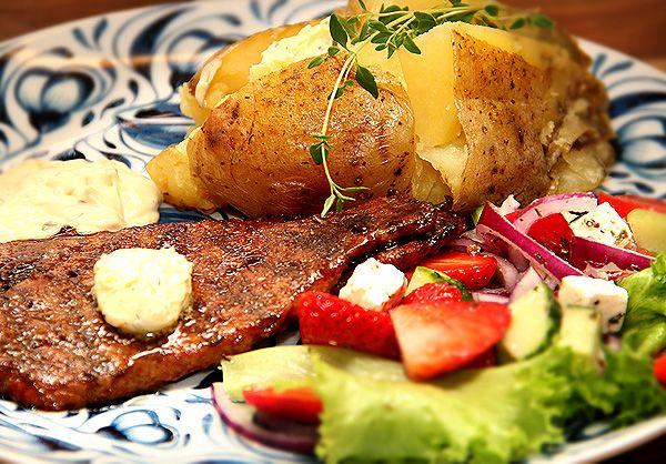 Tunn grillad skinkschnitzel med kryddig marinad. Bakad potatis med vitlökssmör.