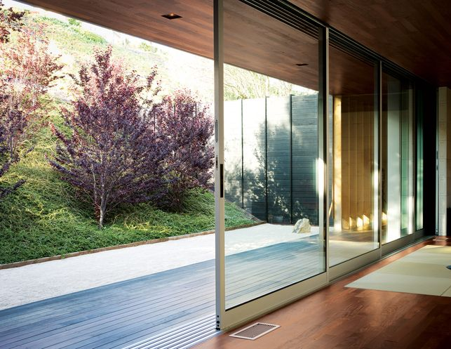 A custom-tailored mechanism allows six floor-to-ceiling sliding glass doors  to open along the entire width of the living space, creating a seamless ...