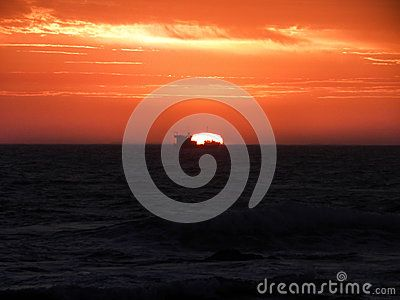 A view of a fishing boat crossing in front of the sun melting into the ocean.
