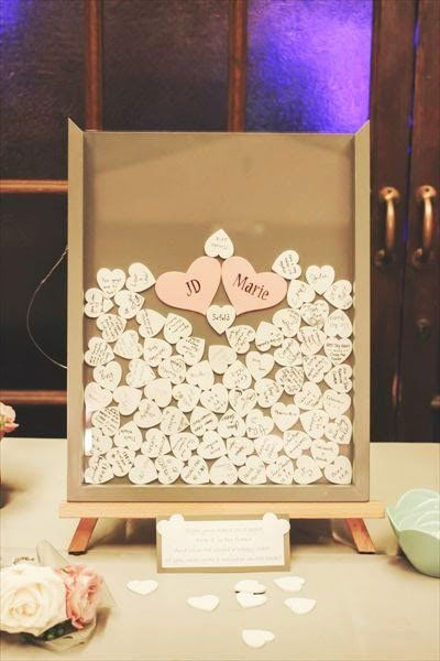 Have each guest sign a small wooden heart and drop it in a shadow box frame. This creative guest book becomes a fun piece of art in your home after the wedding.Photo Credit: Happily Ever After