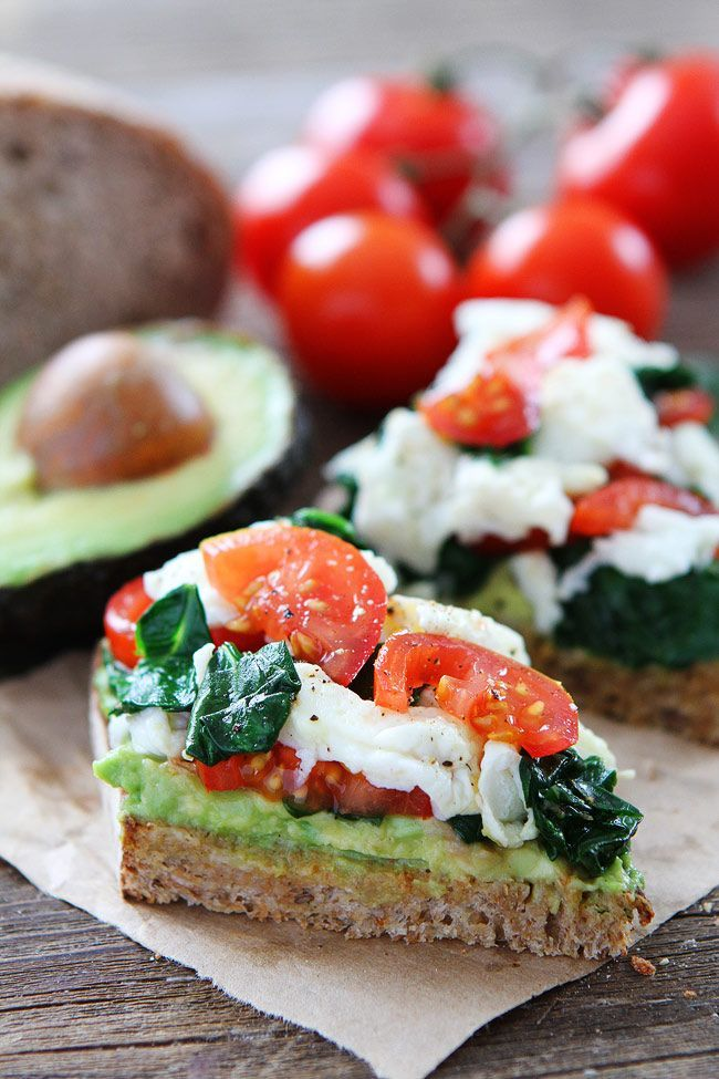 Avocado Toast with Eggs, Spinach, and Tomatoes Recipe on twopeasandtheirpod.com This simple and healthy avocado toast is great for breakfast, lunch, or dinner!