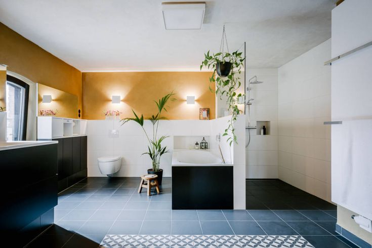 Beautiful bathroom that feels like a wellness spa, with black floors and pot plants. Bad als Wellnessbereich by raumdeuter