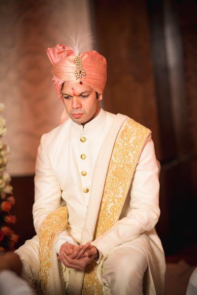 off white sherwani, gold buttons, gold dupatta, pastel pink safa, gold kalgi