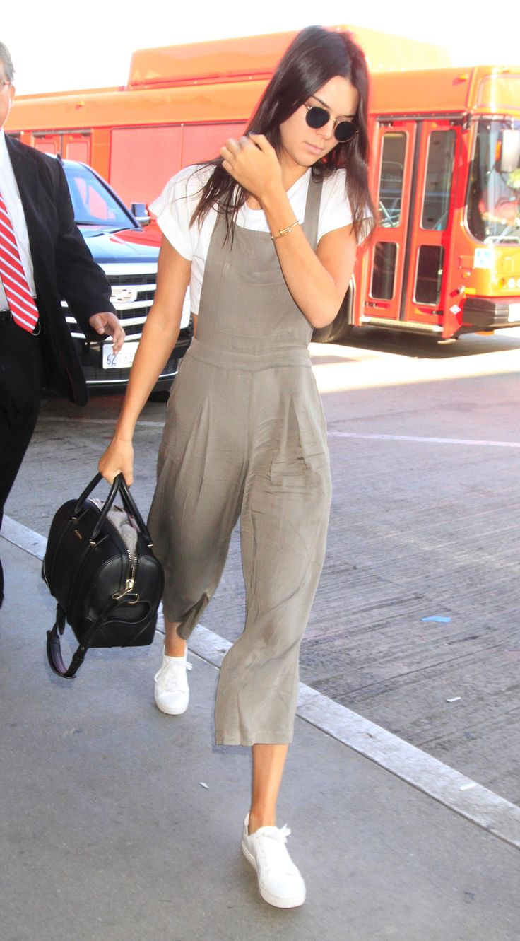 Kendall Jenner in a taupe Forever 21 jumpsuit, a white crop top, round sunglasses, and white sneakers