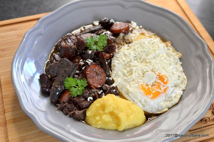 "Tochitura moldoveneasca reteta traditionala. Bucatele fragede, rumene de carne, organe de porc si carnati ""topite"" in untura, servite cu oua ochi si branza"