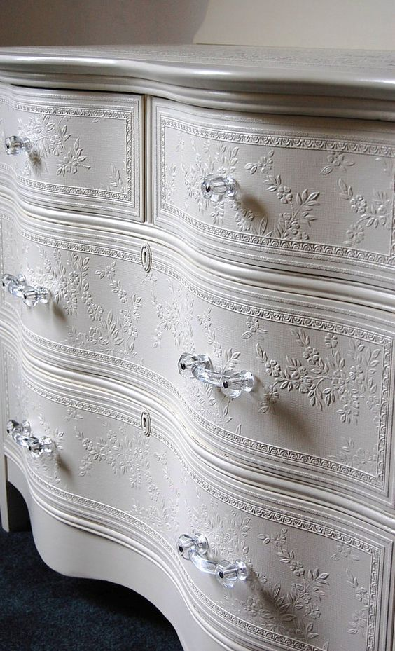 White shabby chic painted dresser with embossed white floral wallpaper on the dr…