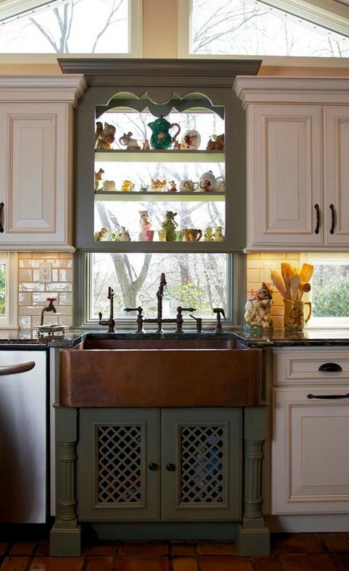 Signature Hardware's Fiona Hammered Copper Farmhouse Sink looks beautiful paired with these cream and green kitchen cabinets.