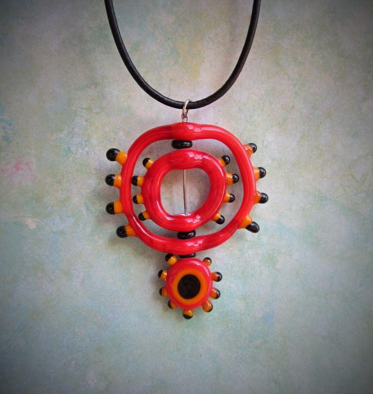 Květina+z+Marsu+Skleněný+autorský+šperk+v+barvě+červené+zavěšený+na+kulaté+černé+kůžičce.+Vyroben+nad+kahanem+kombinací+techniky+taženého+a+vinutého+skla.+Velikost+šperku+53+x+45+mm+(včetně+nálepů,+ale+bez+kovového+očka).+Zapínání+na+karabinu+z+obecného+kovu+v+barvě+stříbrné+++prodlužovací+řetízek.