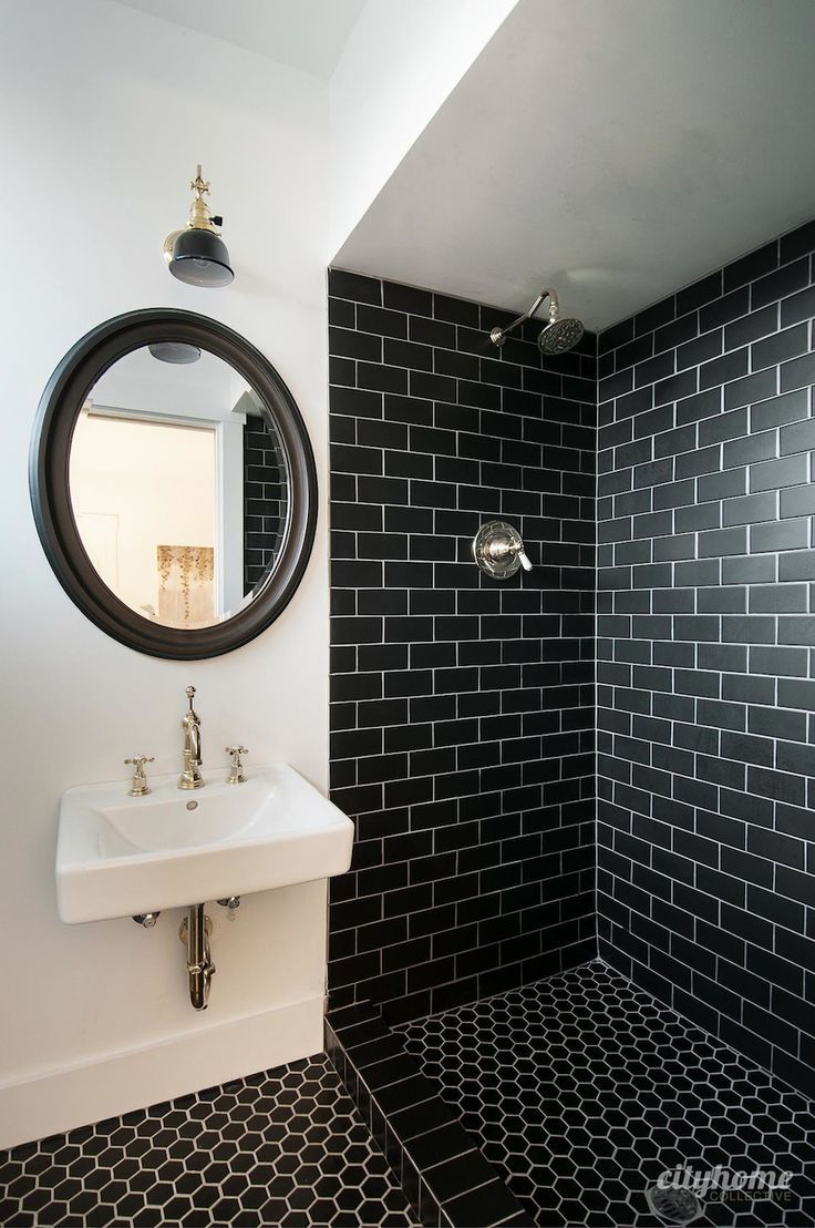 Modern bathroom. Black subway tile, brass fixtures, white wall mounted sink. Beautiful.