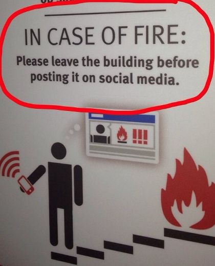 Sign - In Case of Fire, Please exit before posting on social media