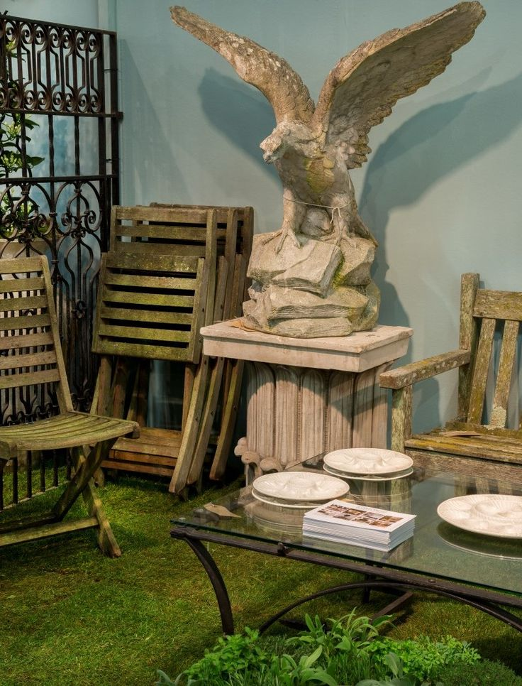 A splendid and vast stone eagle sits atop a marble column; vintage wooden garden chairs and table at Jackdawes Antiques.