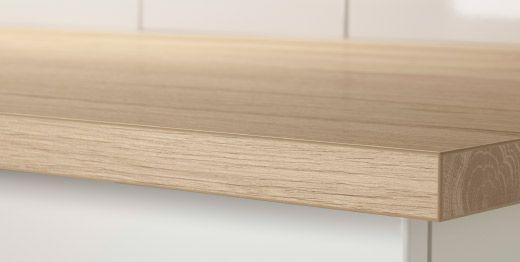Nærbillede af en bordplade af laminat efter mål med lyst egetræsmønster.