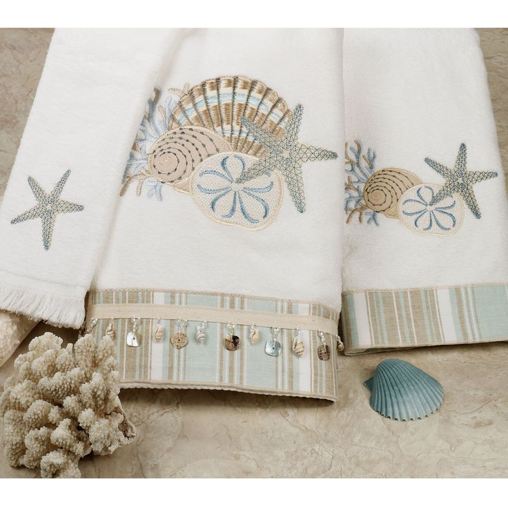 """By the Sea Embroidered Bath TowelsWhite, pure cotton towel set has stripes and shell and coral designs in colors of sea blue and sand brown. Set includes bath towel, 25""""x50""""; hand towel, 17""""x30""""; and fingertip towel, 12""""x19"""". Bath towel has bead and shell accents. Machine wash $55.99"""