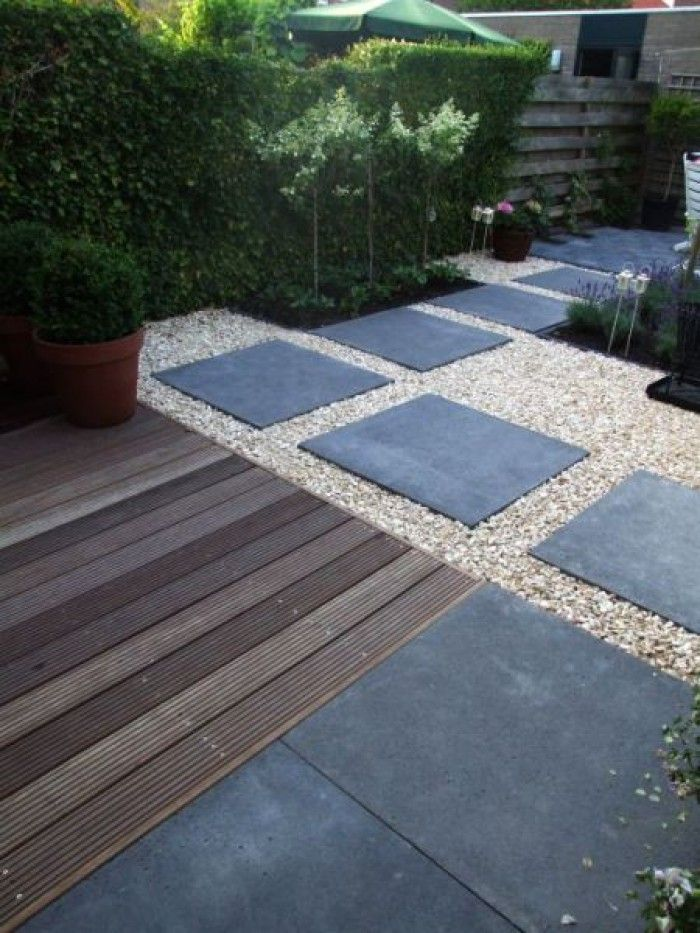 Formal areas can look cold and uninviting but you can soften and warm up the space using a mix of materials such as wooden deck boards with gravel and slate slabs.