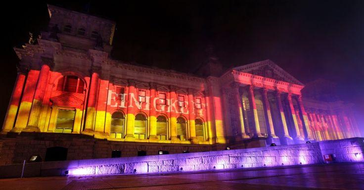 """O Reichstag, sede do Parlamento Federal Alemão, em Berlim, é iluminado com as cores da bandeira do país durante a festa de comemoração do 25º aniversário da reunificação da Alemanha. No texto, lê-se """"Unidade"""". Os alemães celebram em 3 de outubro o Dia da Unidade alemã, quando a Alemanha ocidental e oriental voltaram a ser um só território em 1990. A data é feriado nacional"""