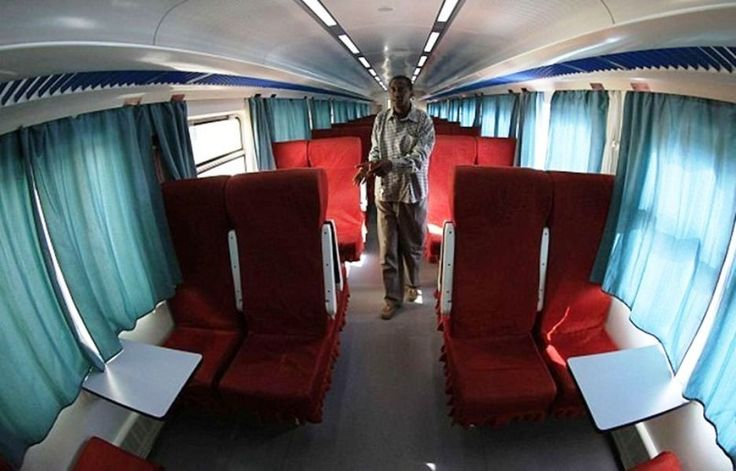 """A man walks down the aisle of Sudan's new Nile Train, in Khartoum.  On January 20 the train began daily passenger service - Sudan's first in years - as part of efforts to revive the railway system despite an economic crisis that has left the country ravaged by inflation and starving for hard currency. """"This new train is really, really modern,"""" says Ahmed Hussein, the project manager for Sudan Railways Corporation."""