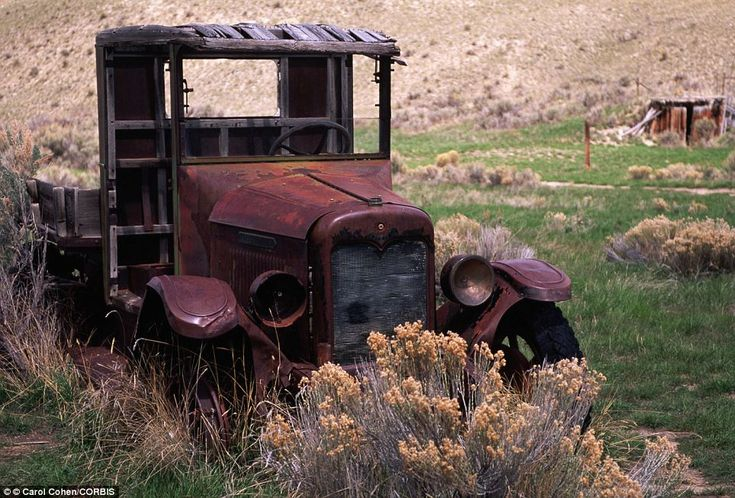 Antique: Reds, greens, and golds mark various stages of rust development on an abandoned truck near the ghost town