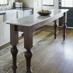 A long, slender table that might have originally occupied a hall, entry, or dining room stands in for an island in this kitchen. Its slender width makes it ideal for a narrow kitchen, and at 36 inches tall, it sits at a convenient height for food prep or