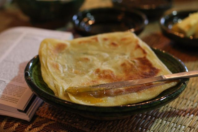 Photographs and instructions for how to fold and cook msemen, square-shaped Moroccan pancakes.