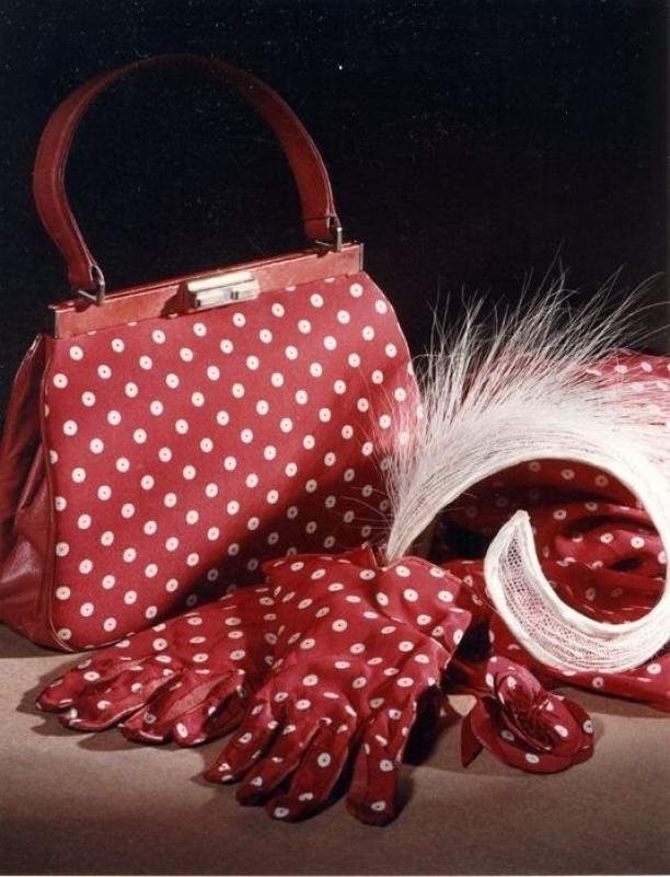 Handtas van koraalrood leer bekleed met rode zijde met witte noppen, rechthoekige metalen beugel en leren draaglus | Modemuze