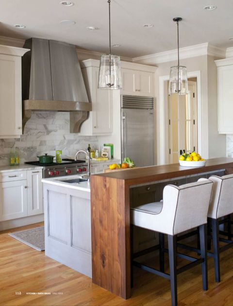 white cabinets with grey island, lighting fixtures back splash