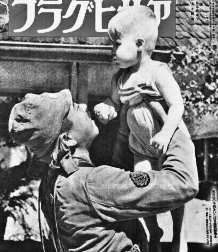 """Front Cover of the Magazine """"Asahi Graph"""" Showing a Japanese Soldier holding a baby of the German colonist in Batavia, Dutch East Indies, 1942"""