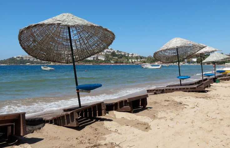 Kadikalesi Beach, #Bodrum Peninsula Turkey. Kekik Cafe has tables and chairs available on their wooden patio. They also have umbrellas and wooden loungers located on the sand.