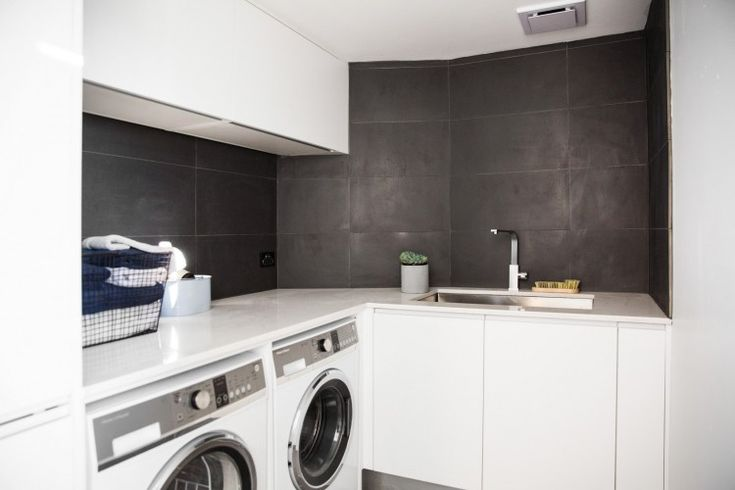 Simple, contemporary and stylish laundry featuring grey wall tiles and white cabinetry. Large laundry with generous bench space and rectangular sink, talk about laundry inspiration!