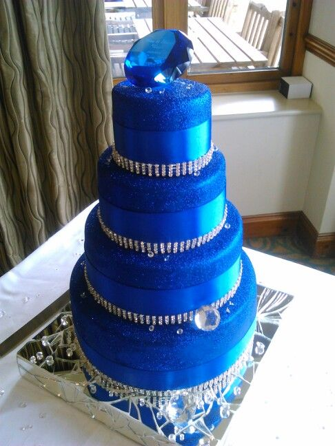 Sparkly royal blue wedding cake. Blue icing, edible blue glitter coat, satin and diamante ribbon, small edible jelly diamonds and large glass diamonds to decorate, handmade mirror base to reflect its beauty. Really proud of my creation, unique and perfect xxxx