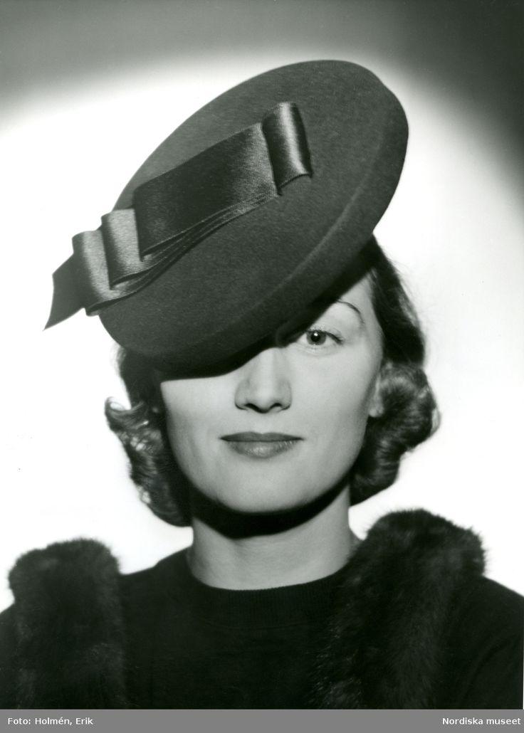 1939. Porträtt av kvinna i hatt med sidenband. Foto: Erik Holmén