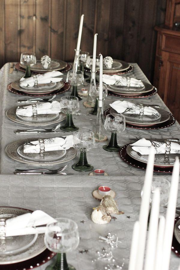 Dukning nyår 2012. Nyårsdukning i silver, grått och rött. Undertallrikar som är röda och tallrikar i grått och glas. Ljusslinga på bordet och en hemgjord ljusstake av drivved. Silverbestick och servettringar i silver från Cervera. New years table setting.