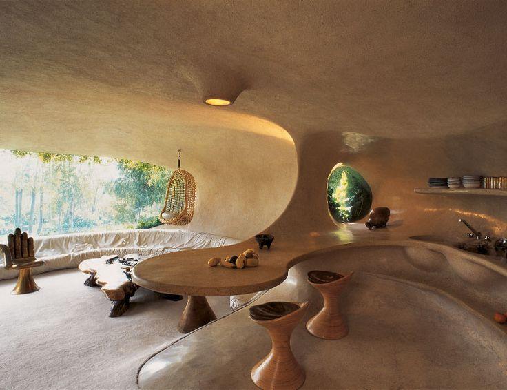 La folie organique de Javier Senosiain Aguilar (Mexique) Le living, avec vue sur le jardin, est délimité par un canapé circulaire revêtu de cuir blanc. La Chaise Main est signée Pedro Friedeberg, la table basse faite avec un tronc de séquoia et le fauteuil suspendu (inaccessible!) est en moelle de bois. Ouverte sur le living, la cuisine-salle à manger, au premier plan, est inspirée par la spirale d'un coquillage.