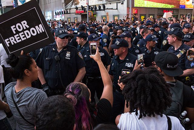 Demonstrators record a crowd of police officers on hand in New York's Times Square, where a large crowd protested after fatal police shootings in Louisiana and Minnesota, July 7, 2016. (Photo: Christopher Lee / The New York Times)