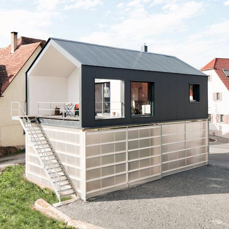 This black house by Fabian Evers Architecture and Wezel Architektur is raised up over a translucent base where the client's truck can be stored.