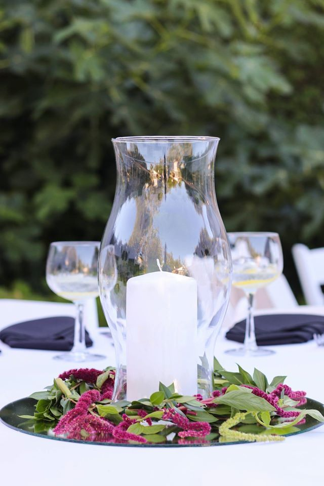 Hurricane Lamp centerpieces with mirrors on the bottom. We added colorful mossy greens for a nice pop of color. An elegant and simple affordable option for those not wanting to have flowers.