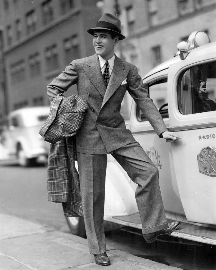 Caroline Snead. This picture shows mens fashion in the late 30s. They wore their coats a little longer than their waist and the pants had a crease going down the middle of them.